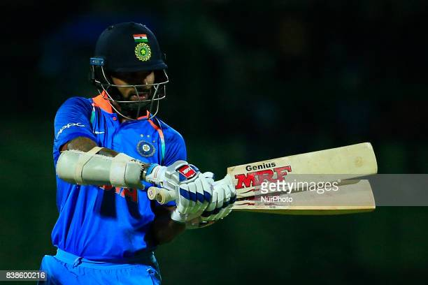 Indian cricket team's opening batsman Shikhar Dhawan tries out a bat from his collection of bats during the 2nd One Day International cricket match...