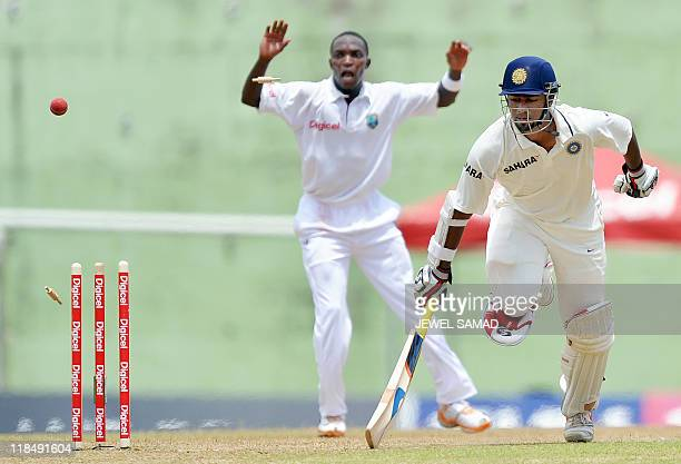 Indian cricketer Abhinav Mukund foils a run out attempt by West Indies cricketers as bowler Fidel Edwards reacts during the third day of third and...