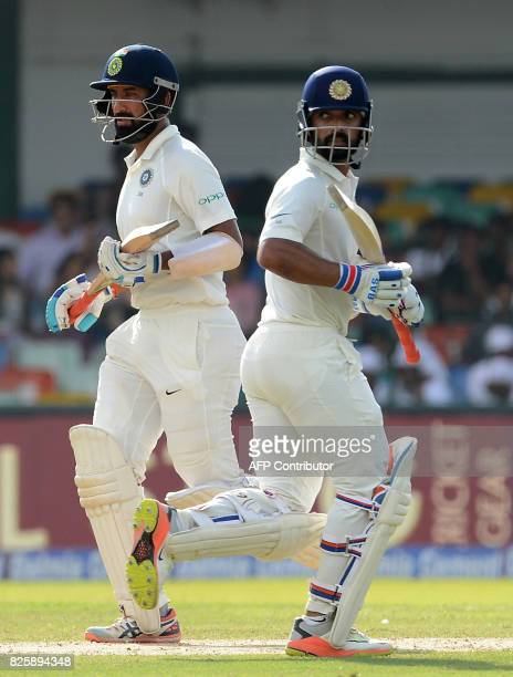 Indian cricketer Ajinkya Rahane and teammate Cheteshwar Pujara run between the wickets during the first day of the second Test match between Sri...