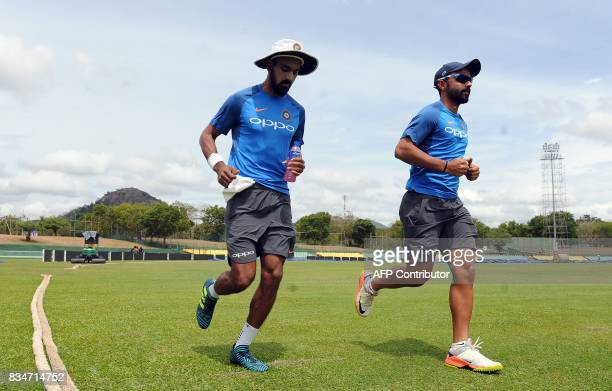 Indian cricketer Ajinkya Rahane and teammate Lokesh Rahul warm up during a practice session at the Rangiri Dambulla International Cricket Stadium in...