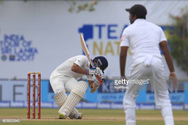 Indian cricketer Ajinkya Rahane loses his balance after facing a ball from Sri Lanka's Nuwan Pradeep during the 2nd Day's play in the 1st Test match...