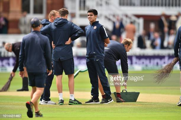 Indian cricketer Arjun Tendulkar is seen as ground staff secure the covers on the pitch during the rain break on the second day of the second Test...