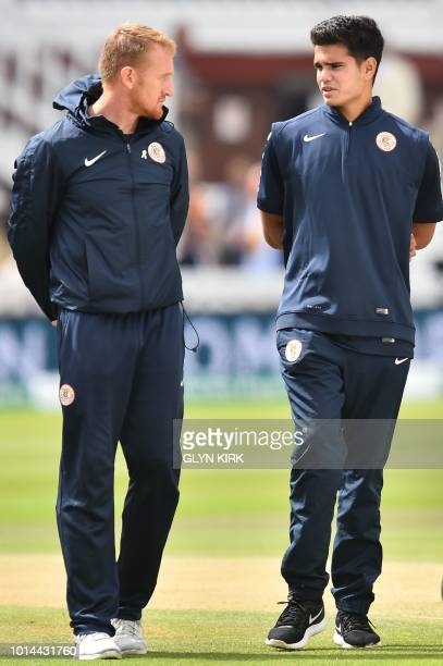 Indian cricketer Arjun Tendulkar talks with MCC head coach Steve Kirby on the pitch during a break for rain on the second day of the second Test...