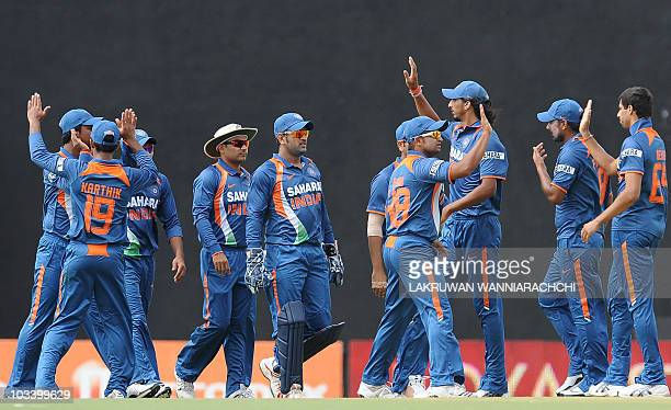 Indian cricketer Ashish Nehra celebrates with teammates after the dismissal of unseen Sri Lankan cricket captain Kumar Sangakkara during the third...