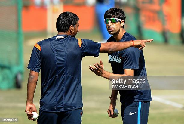 Indian cricketer Ashish Nehra gestures as he speaks with teammate Praveen Kumar during a training session at The Swai Mansingh Cricket Stadium in...