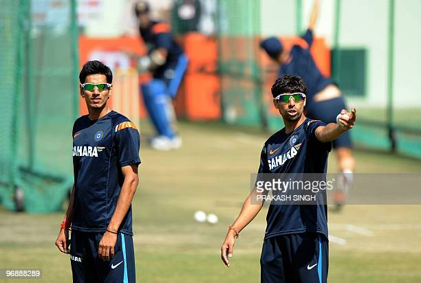 Indian cricketer Ashish Nehra is watched by teammate Sudeep Tyagi as he gestures during a training session at The Swai Mansingh Cricket Stadium in...