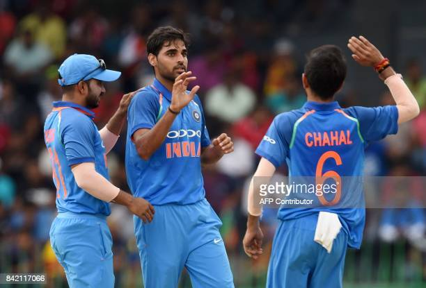 Indian cricketer Bhuvneshwar Kumar celebrates with his teammates after he dismissed Sri Lankan cricketer Niroshan Dickwella during the final one day...