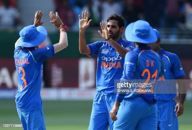 Indian cricketer Bhuvneshwar Kumar celebrates with teammates after he dismissed Bangladesh batsman Liton Das during the one day international Asia...