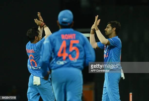 Indian cricketer Bhuvneshwar Kumar celebrates with teammates after he dismissed Sri Lankan cricketer Upul Tharanga during the Twenty20 international...