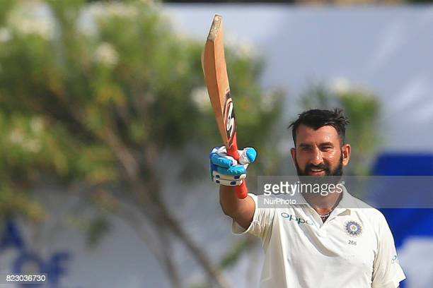 Indian cricketer Cheteshwar Pujara celebrates after scoring 100 runs during the 1st Day's play in the 1st Test match