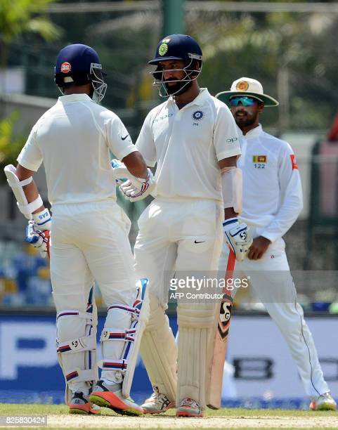Indian cricketer Cheteshwar Pujara is congratulated by teammate Ajinkya Rahane after scoring a halfcentury during the first day of the second Test...