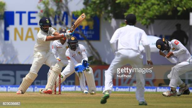 Indian cricketer Cheteshwar Pujara plays a shot as Sri Lanka's Kusal Mendis reacts during the 1st Day's play in the 1st Test match