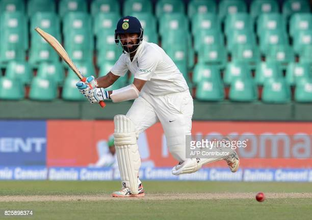 Indian cricketer Cheteshwar Pujara plays a shot during the first day of the second Test match between Sri Lanka and India at the Sinhalese Sports...