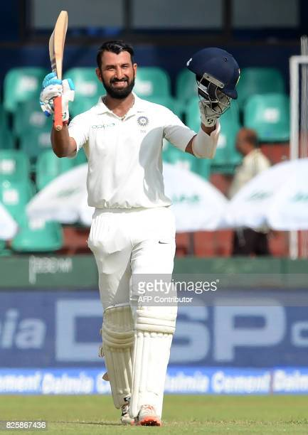 Indian cricketer Cheteshwar Pujara raises his bat and helmet in celebration after scoring a century during the first day of the second Test match...