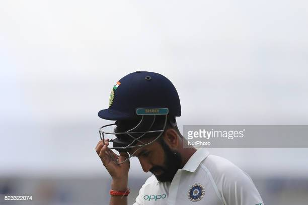 Indian cricketer Cheteshwar Pujara removes his helmet while walking back to the pavilion after his dismissal during the 2nd Day's play in the 1st...