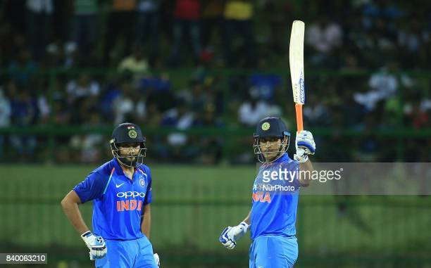Indian cricketer MS Dhoni raises his bat after scoring 50 runs as Rohit Sharma looks on during the 3rd One Day International cricket match between...