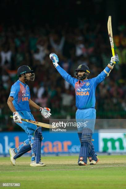 Indian cricketer Dinesh Karthik celebrates after hitting a six off the last ball during the final Twenty20 cricket match of NIDAHAS Trophy between...