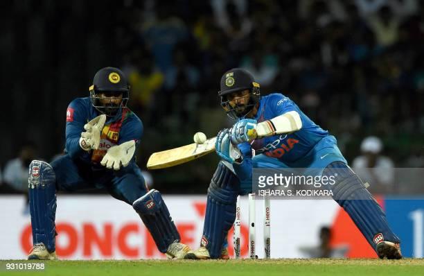 TOPSHOT Indian cricketer Dinesh Karthik plays a shot as Sri Lankan cricketer Kusal Perera looks on during the fourth Twenty20 international cricket...
