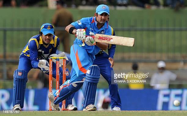 Indian cricketer Gautam Gambhir plays a shot as wicketkeeper Dinesh Chandimal reacts during the fifth and final oneday international match between...