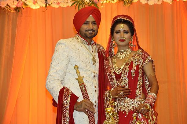Indian cricketer Harbhajan Singh poses with his wife Geeta Basra during their marriage ceremony in Jalandhar on October 29 2015 / AFP PHOTO / SHAMMI..