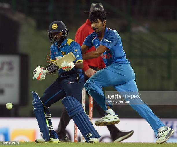 Indian cricketer Jasprit Bumrah runs to the ball next to Sri Lankan cricketer Akila Dananjaya during the second one day international cricket match...
