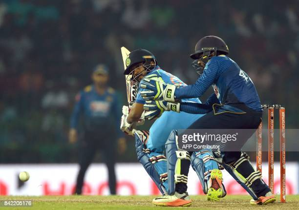 Indian cricketer Kedar Jadhav is watched by Sri Lankan wicketkeeper Niroshan Dickwella as he plays a shot during the final one day international...