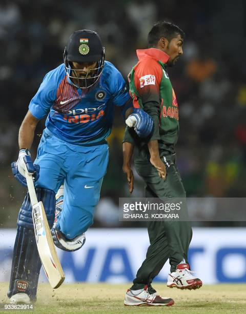 Indian cricketer Lokesh Rahul runs between the wickets as Bangladeshi cricketer Nazmul Islam looks on during the final Twenty20 international cricket...