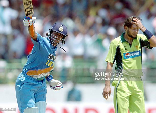 Indian cricketer Mahender Dhoni celebrates after scoring a century as Pakistani bowler Shahid Afridi holds his head during the second one day...