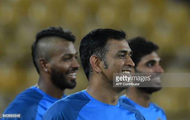 Indian cricketer Mahendra Singh Dhoni Bhuvneshwar Kumar and Hardik Pandya look on during a practice session at The RPeremadasa Stadium in Colombo on...