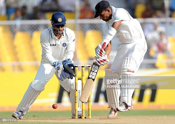 Indian cricketer Mahendra Singh Dhoni looks on as Sri Lankan cricketer Thilan Samaraweera batson the third day of the first test between India and...