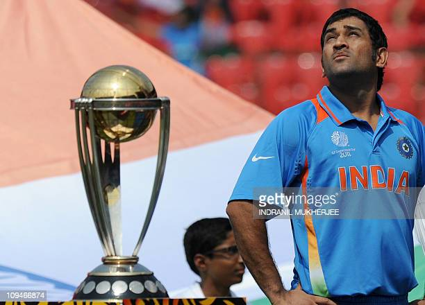 Indian cricketer Mahendra Singh Dhoni looks skywards while standing next to The ICC Cricket World Cup 2011 trophy before the start of the ICC Cricket...