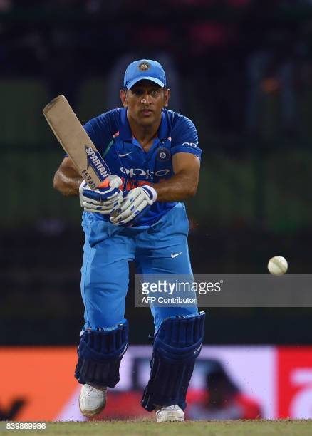 Indian cricketer Mahendra Singh Dhoni plays a shot during the third one day international cricket match between Sri Lanka and India at the Pallekele...
