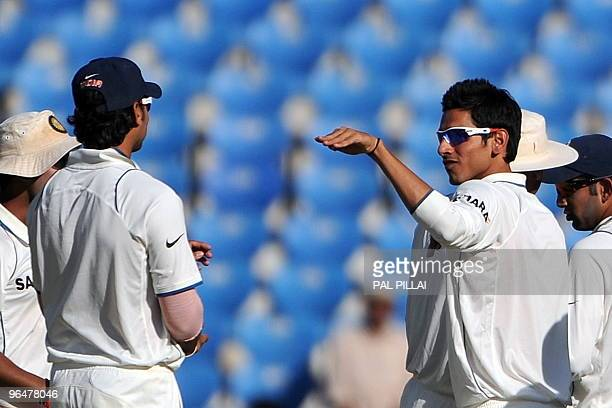 Indian cricketer Murali Vijay gestures to teammate Sudeep Tyagi during a drinks break on the second day of the first cricket Test match between India...