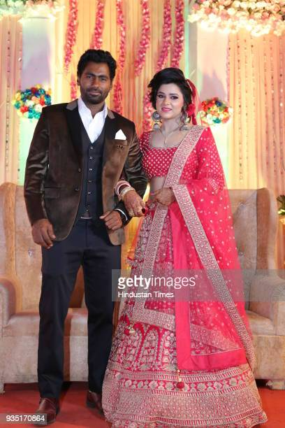 Indian cricketer Parvinder Awana and Sangit Awana pose for photographers during their wedding reception at Shiv Garden on March 10 2018 in Greater...