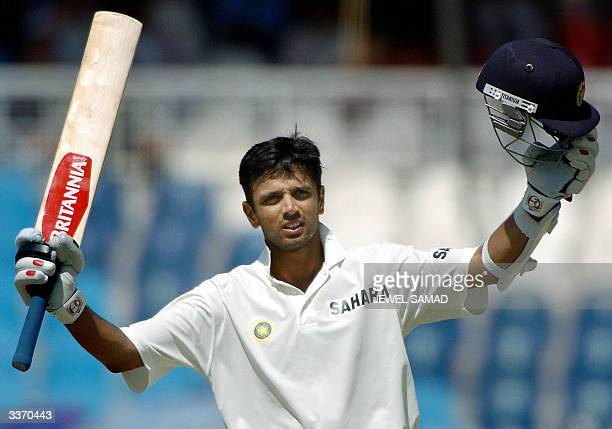 Indian cricketer Rahul Dravid raises his bat and helmet after reaching his double century during the third day of the third and final Test match...