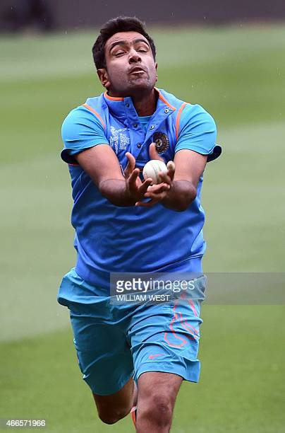 Indian cricketer Ravi Ashwin takes a catch during a training session ahead of their 2015 Cricket World Cup quarterfinal match against Bangladesh in...