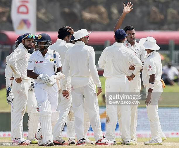 Indian cricketer Ravichandran Ashwin and teammates celebrate after dismissing Sri Lankan batsman Dhammika Prasad during the first day of the opening...