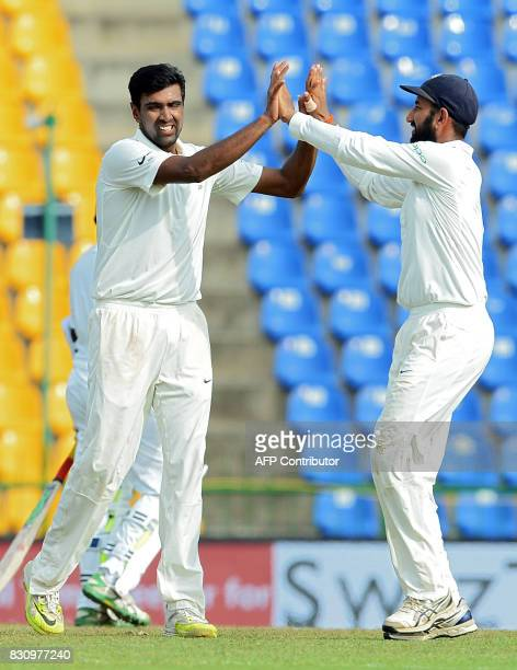 Indian cricketer Ravichandran Ashwin celebrates with his teammate Cheteshwar Pujara after he dismissed Sri Lankan cricket captain Dinesh Chandimal...