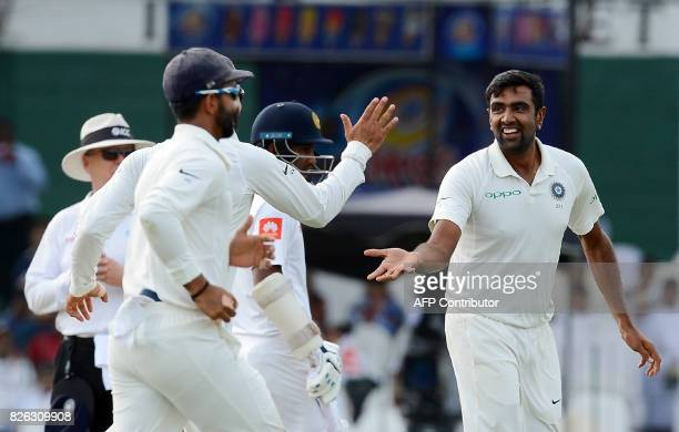 Indian cricketer Ravichandran Ashwin celebrates with his teammates after he dismissed Sri Lankan cricketer Upul Tharanga during the second day of the...