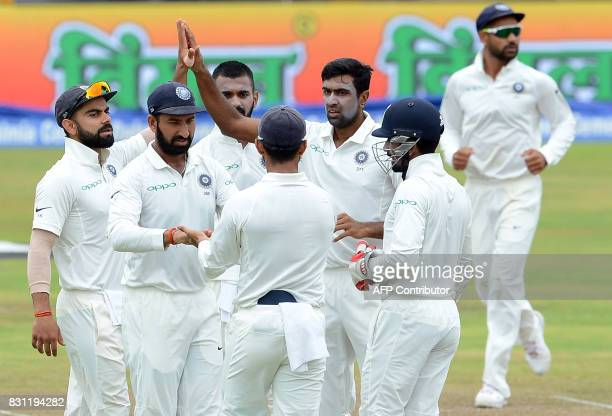 Indian cricketer Ravichandran Ashwin celebrates with his teammates after he dismissed Sri Lankan cricketer Dimuth Karunaratne during the third day of...