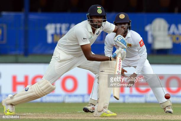 Indian cricketer Ravichandran Ashwin plays a shot in front of Sri Lanka's Kusal Mendis during the second day of the second cricket Test match between...