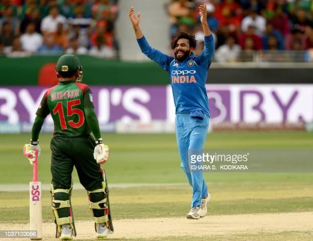 Indian cricketer Ravindra Jadeja celebrates after he dismissed Bangladesh batsman Mohammad Mithun as as Bangladeshi batsman Mushfiqur Rahim looks on...