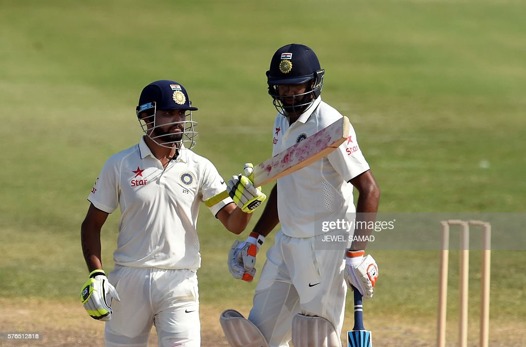 Indian cricketer Ravindra Jadeja (L) celebrates scoring his half-century (50 runs) during Day 2 of the three-day tour match between India and WICB President's XI squad at the Warner Park stadium in Basseterre, Saint Kitts, on July 15, 2016. / AFP / Jewel SAMAD
