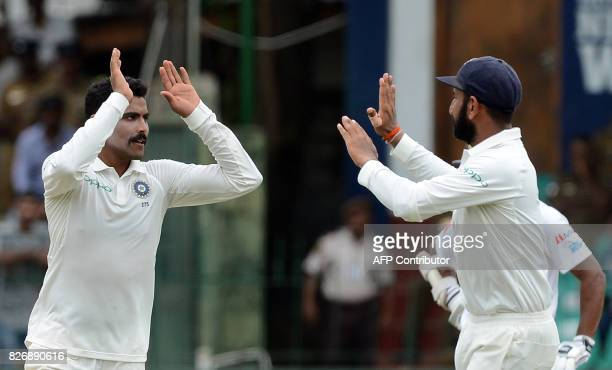 Indian cricketer Ravindra Jadeja celebrates with teammate Cheteshwar Pujara after dismissing Sri Lankan cricketer Dhananjaya de Silva during the...
