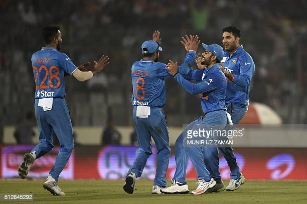Indian cricketer Ravindra Jadeja celebrates with teammates after the dismissal of the Pakistan cricketer Sarfraz Ahmed during the match between India...