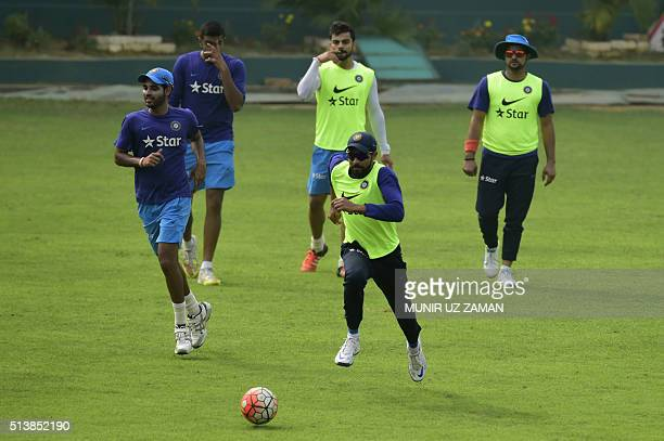 Indian cricketer Ravindra Jadeja plays football with teammates during a training session at the ShereBangla National Cricket Stadium in Dhaka on...