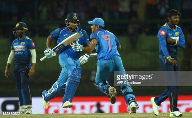 Indian cricketer Rohit Sharma and Mahendra Singh Dhoni run between the wickets during the third one day international cricket match between Sri Lanka...