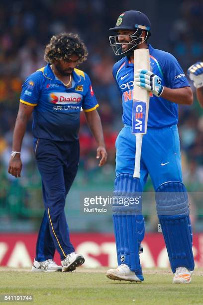 Indian cricketer Rohit Sharma celebrates after scoring 100 runs as Sri Lankan capatin Lasith Malinga walks by during the 4th One Day International...