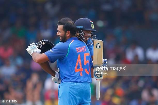 Indian cricketer Rohit Sharma celebrates after scoring 100 runs as Hardik Pandya hugs him during the 4th One Day International cricket match between...