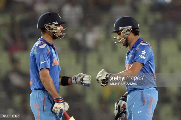 Indian cricketer Rohit Sharma celebrates with teammate Virat Kohli after hitting a boundary during the ICC World Twenty20 tournament Group 2 cricket...